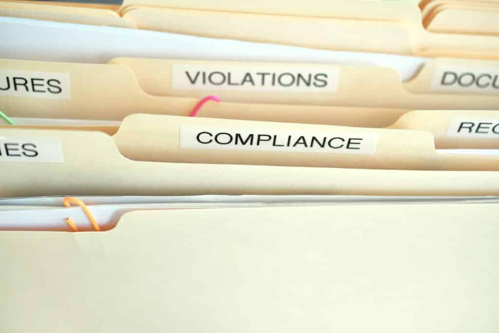 File folders titled compliance, and violations
