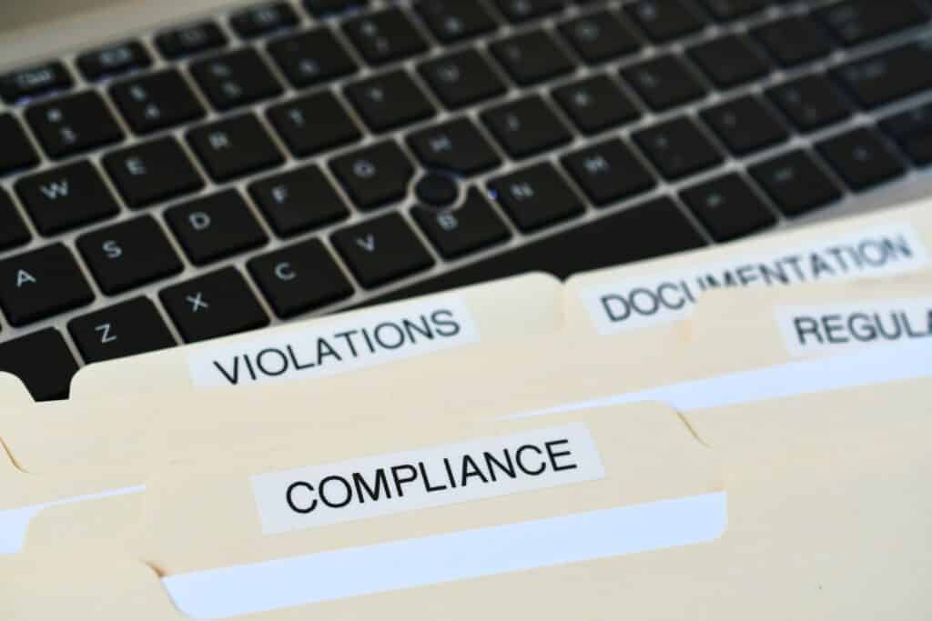 Files folders titled violations, compliance, regulation, and documentation